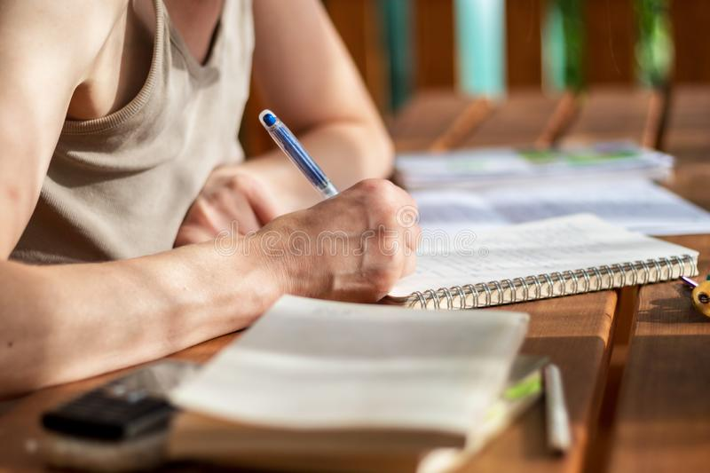 Close-up view of a woman`s hand with a pen, writes in a notebook stock image
