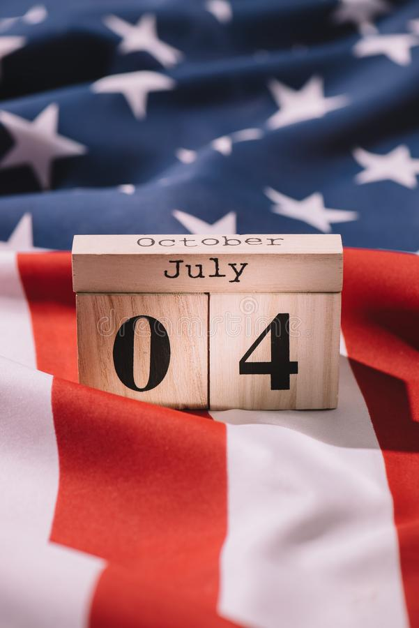 Close up view of wooden calendar with 4th july date on american flag, americas independence. Day concept royalty free stock photo