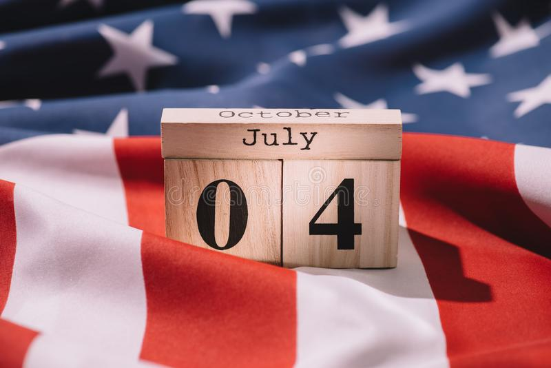 Close up view of wooden calendar with 4th july date on american flag, americas independence. Day concept stock photos