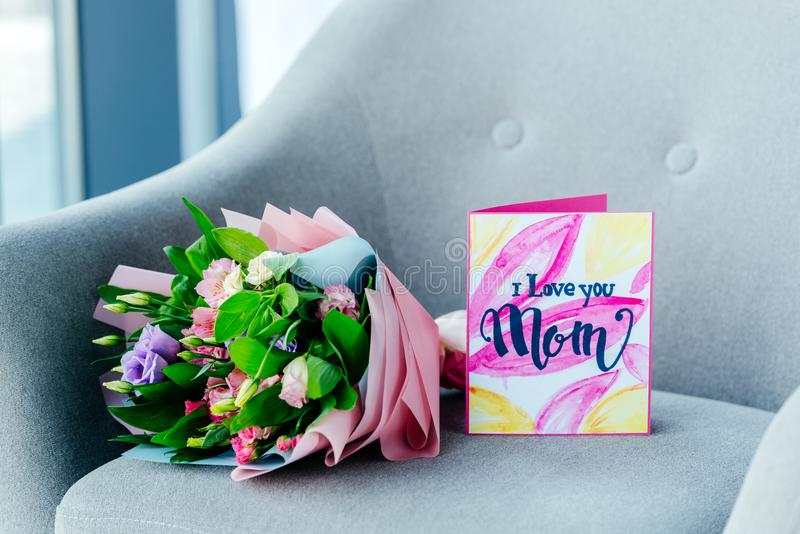 close up view of wrapped bouquet of flowers and i love you mom greeting postcard on armchair, mothers stock photo