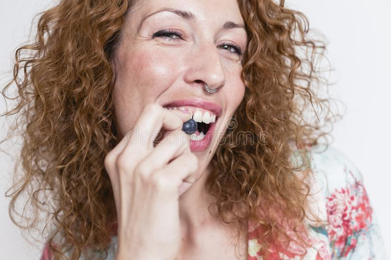 Close up view of a young beautiful woman eating blueberries over white background and smiling. Indoors and lifestyle. Healthy stock images