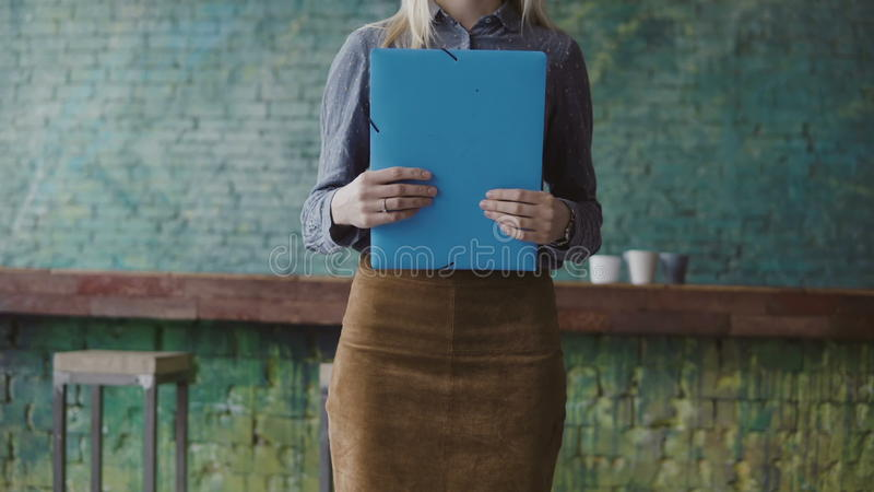Close-up view of young blonde female holding the documents. Woman manager working in modern trendy office. royalty free stock images
