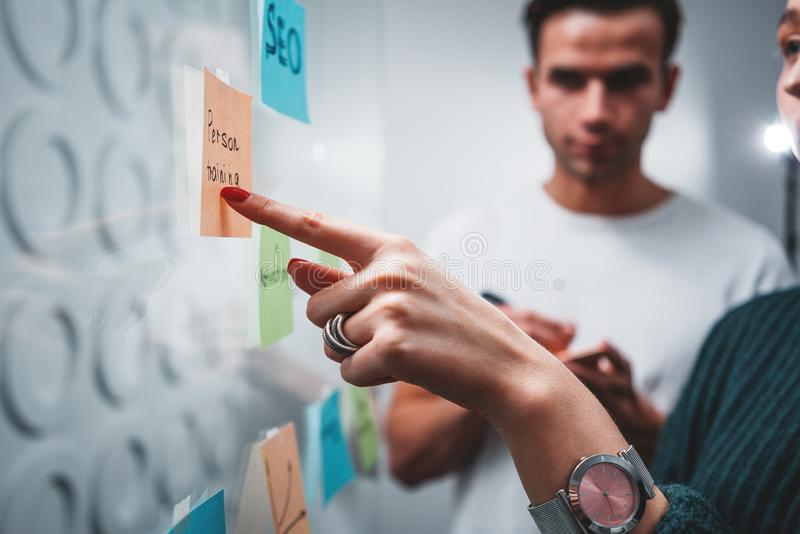 Close-up view of young colleagues hands while posted project plan on note sticky on glass wall in smart office royalty free stock photos