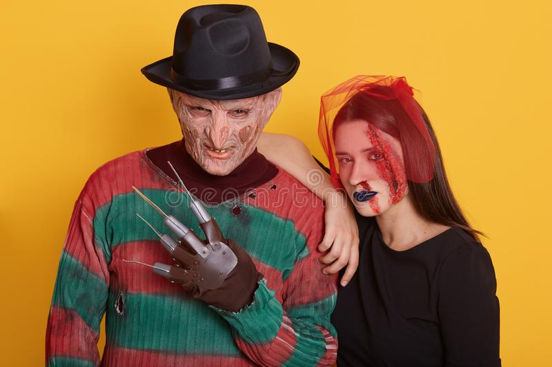 Close up view of young couple wearing halloween costumes, woman and man looking directly at camera, posing isolated over yellow stock images