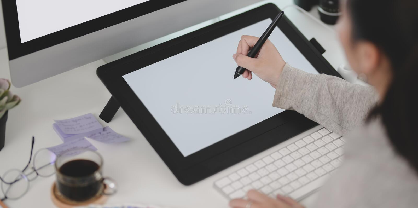 Close-up view of young female designer working on her  project while using tablet stock photo