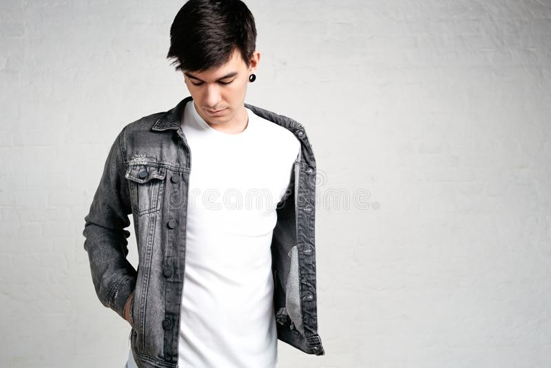 Close up view of young man wearing white t-shirt and jacket royalty free stock photo