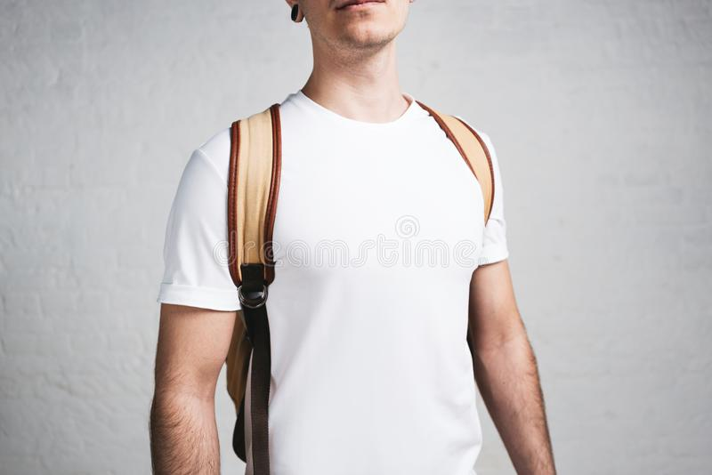 Close-up view of young stylish guy in blank white t-shirt and backpack royalty free stock image