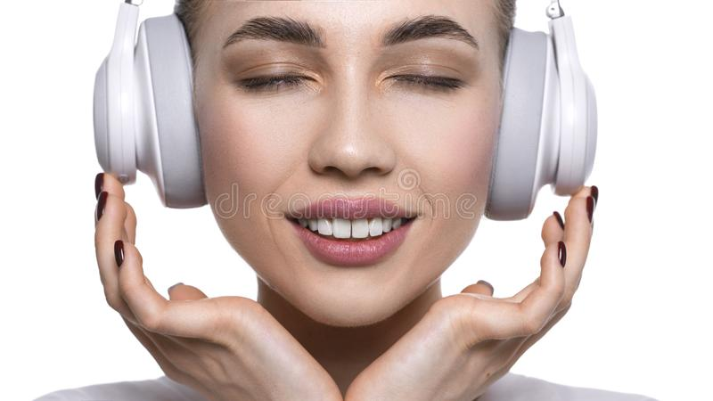 Close up view of a young woman listening to the music via headphones. Isolated on white royalty free stock photo
