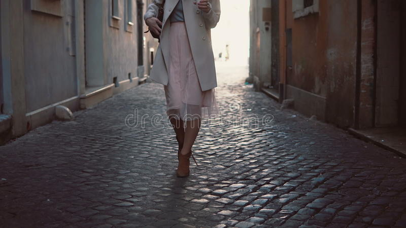 Close-up view of young woman walking at sunny spring city street in Europe. Stylish girl exploring the old town alone. royalty free stock images