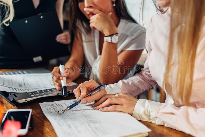 Close-up view of young women working on accounting paperwork checking and pointing at documents sitting at desk in stock photography