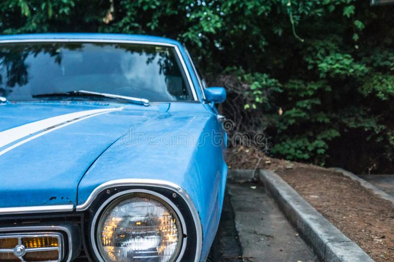 Close up of vintage blue car`s old headlamp. Parked and surrounded by trees royalty free stock images