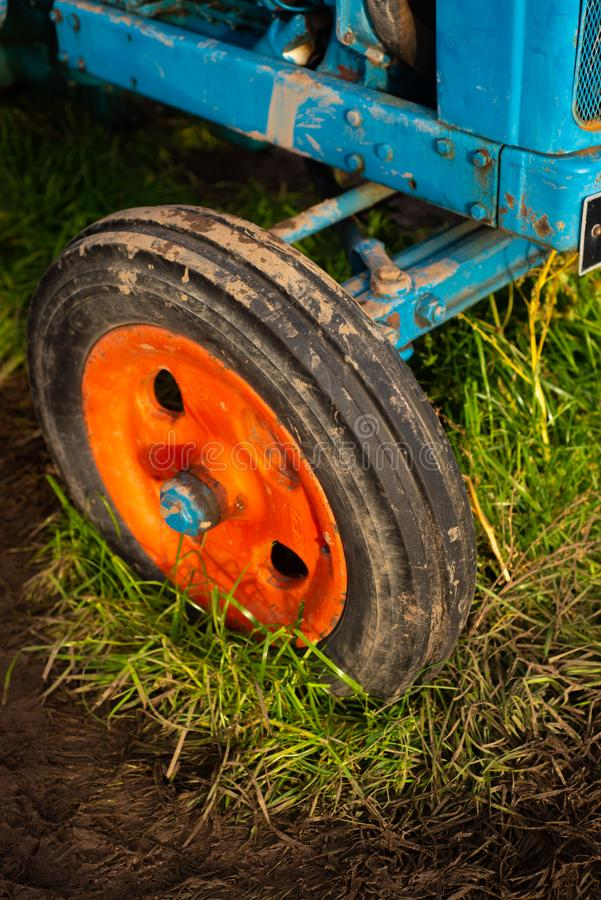 Close Up of a Vintage Blue Tractor With an Orange Wheel in a Muddy Field. Detail from a Muddy Old Fashioned Tractor in a Field on a Farm royalty free stock photos