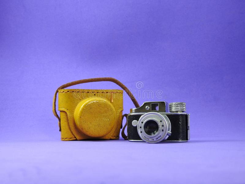 Close-up of a vintage camera miniature with yellow leather case royalty free stock images