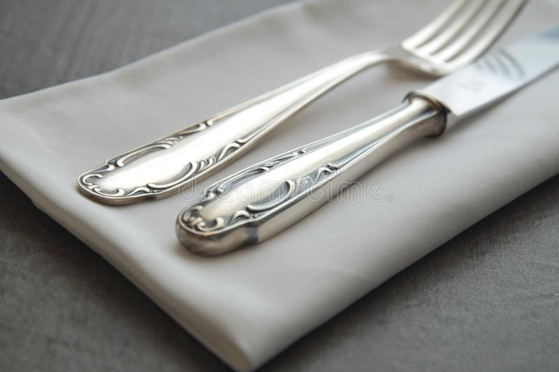 Close up of vintage cutlery and napkin. old antique silverware fork and knife on dark background. stock photos
