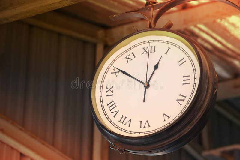 Close up of vintage death clock hang on the vintage zinc roof at vintage train station in province of Asia. Clock in train station with copy space for text royalty free stock photography