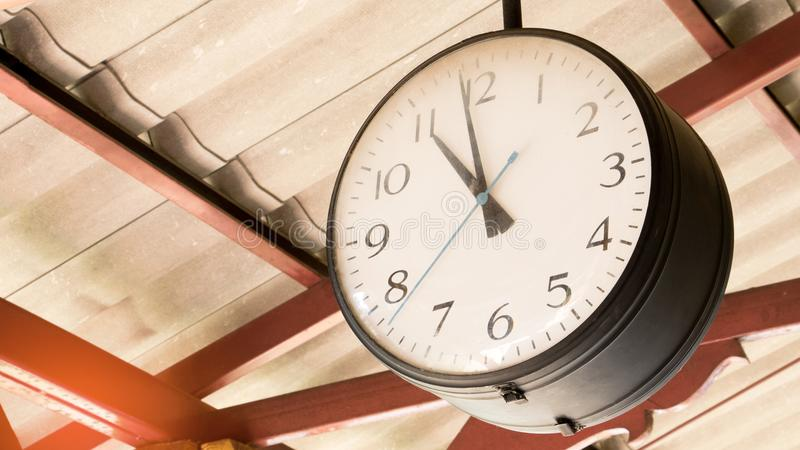 Close up of vintage death clock hang on the vintage zinc roof at vintage train station in province of Asia. Clock in train station with copy space for text royalty free stock photo