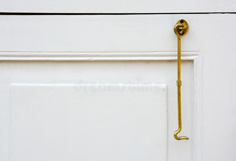 Close up of vintage gold color window hook or brass shutter hook hanging on white wooden window frame background, copy space. Close up of vintage gold color royalty free stock image