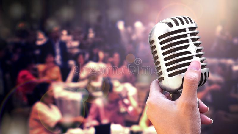 Close up vintage microphone in singer hand singing on stage of wedding event party or business meeting with lighting effect and co stock photo
