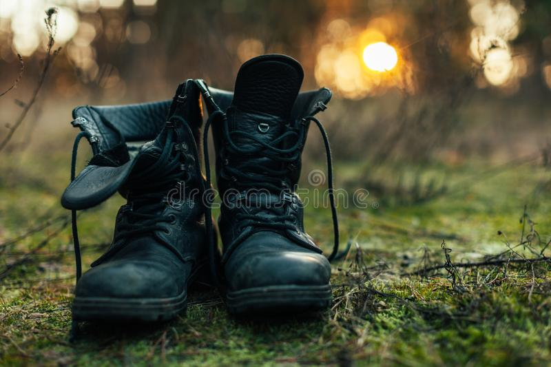 Close up of vintage pair of walking boots on boulder grassland background. Hard travel concept stock photos