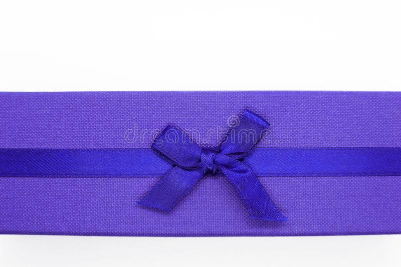 Close up of violet gift box with blue ribbon. On white background with free space for text. Top view flat lay image stock images