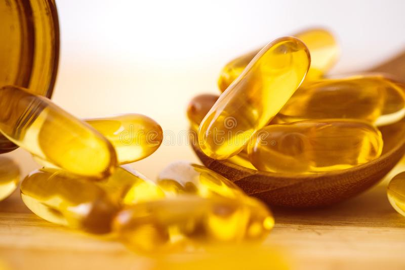 Close up the vitamin D and Omega 3 fish oil capsules supplement on wooden plate for good brain , heart and health eating benefit. Close up vitamin D and Omega 3 stock images