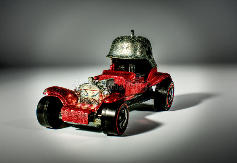 A close up of a vivid, red, metallic toy model car. A close up of a vivid, bright red, metallic toy model car. The car is a hot rod with an unusual germanic stock images