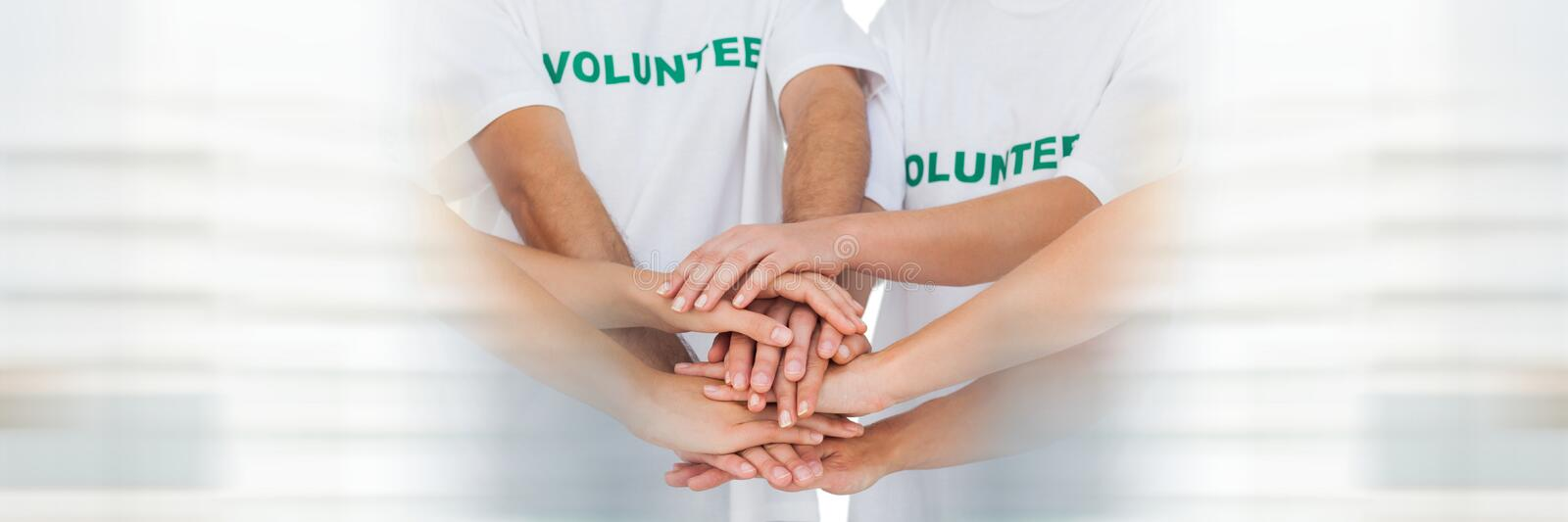 Close up of volunteer team putting hands together and blurry white framing royalty free stock image