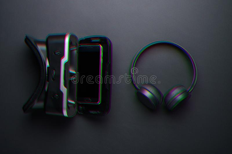Close-up VR glasses with smartphone and wireless headphones, anaglyph and glitch effect.  royalty free stock image
