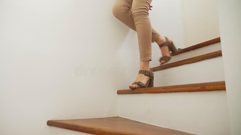 Close-up, vrouwelijke benen in beige nauwsluitende broek en gehielde sandals die langs een houten moderne trap lopen stock afbeeldingen