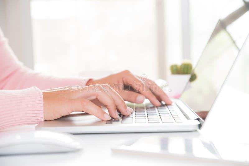 Close-up vrouwelijke handen die op laptop toetsenbord typen Vrouw die thuis Bureau werken royalty-vrije stock fotografie