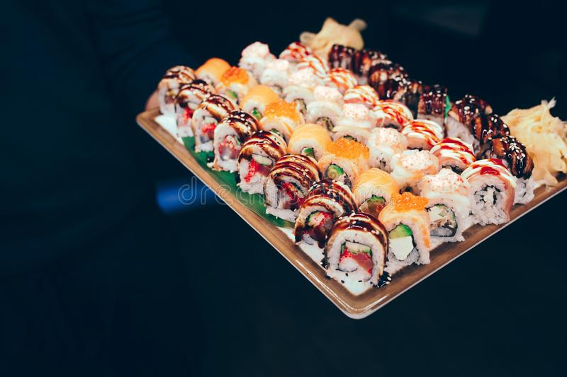 Close-up waiter holding Set of sushi red greed dragon, tuna Hokkaido California Tobico philadelphia roll buffet in night dining re. Staurant. Delicious   served royalty free stock photos