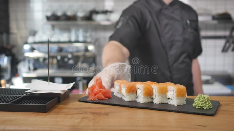 Close-up - the waiter put the sushi on board on the table in restaurant.  royalty free stock images