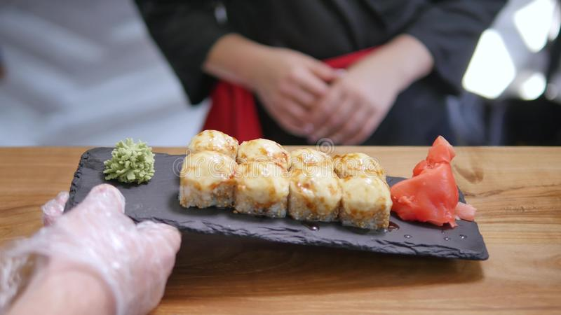 Close-up - the waiter put the sushi on board on the table in restaurant.  royalty free stock photography