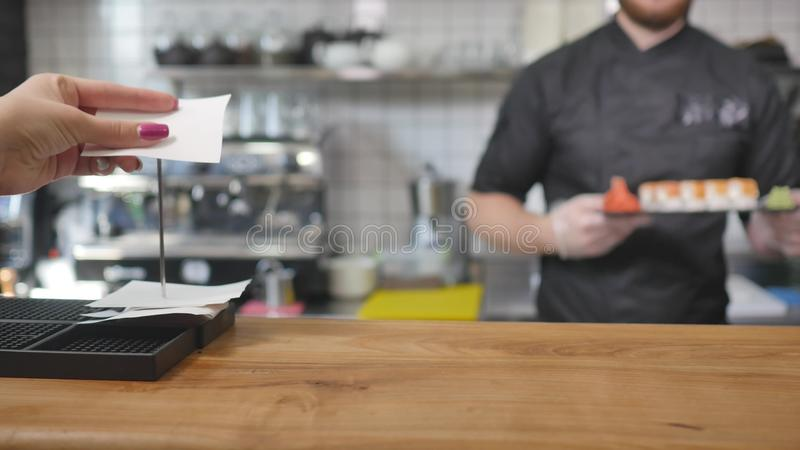 Close-up - the waiter put the sushi on board on the table in restaurant.  royalty free stock photos