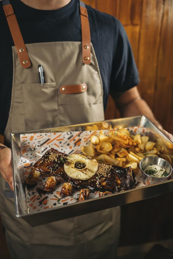 Close-up of a waiter serving delicious barbecued prime rib with french fries royalty free stock image