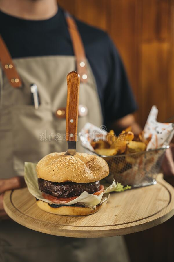 Close-up of a waiter using face mask serving a delicious meat burger with fries stock photos
