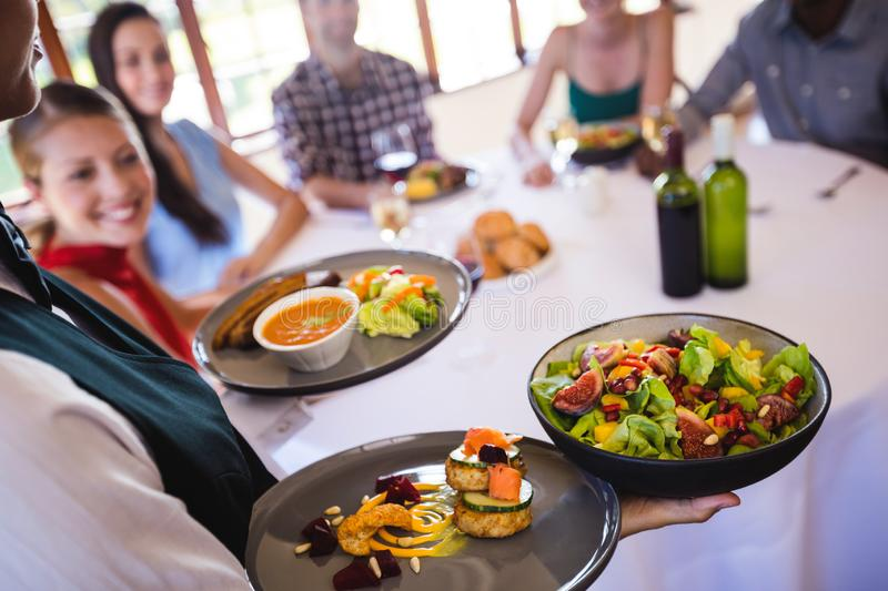 Waitress holding food on plate in restaurant royalty free stock photos