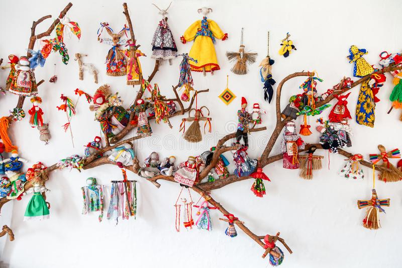 Close up of wall decorated with a large number of dolls. Russian-folk old-fashioned dolls in different dresses made of straw, wood and other materials. Doll for royalty free stock image