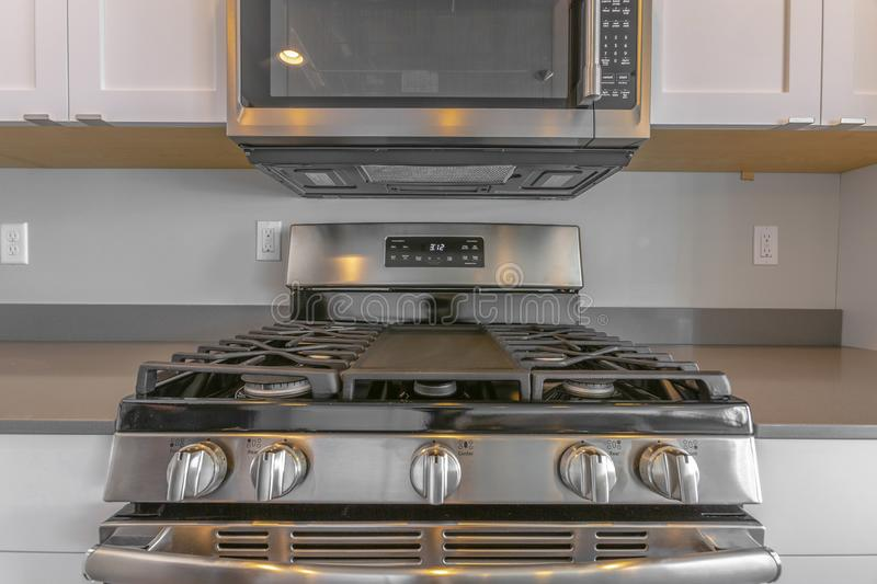 Close up of wall mounted microwave and cooktop of a range inside the kitchen. Wooden cabinets can also be seen against the gray wall of this room stock photo