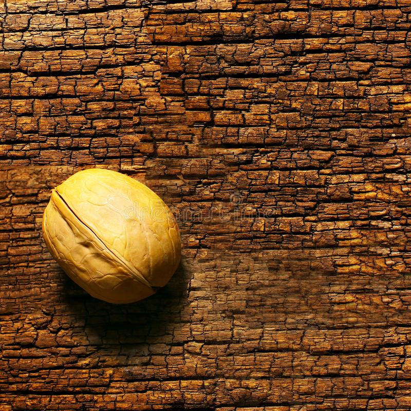 Close-up of a walnut on an old wooden table with a distinct structure, space for text. Close-up of a walnut royalty free stock photography