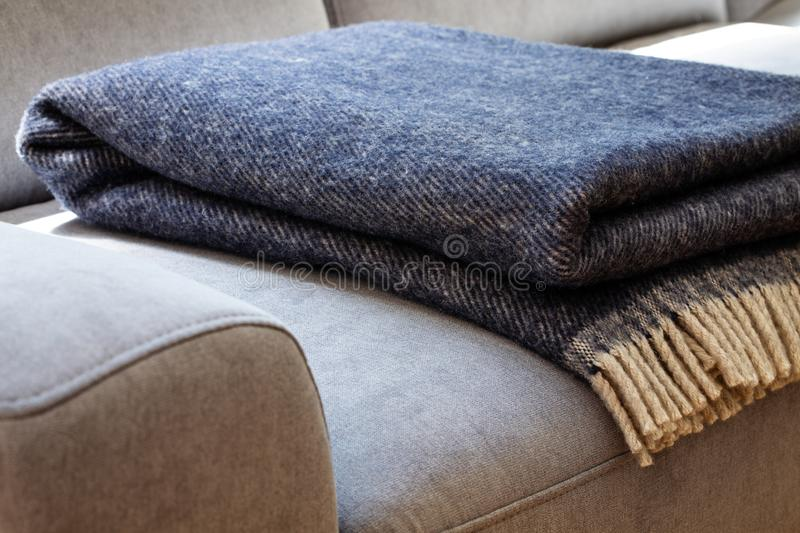 Close-up of a warm, navy blue, wool blanket with beige fringe on a comfy, gray sofa in a cozy living room interior stock images