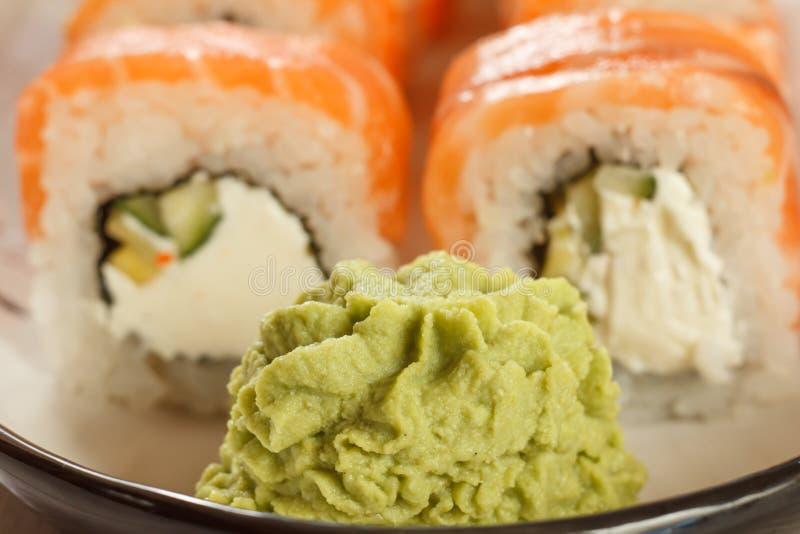 Close up wasabi with sushi rolls Uramaki Philadelphia on the background on ceramic plate. Japanese cuisine royalty free stock image