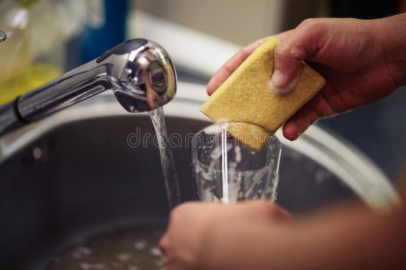 Close up washing dishes. male hands in foam washes the frying pa royalty free stock photo