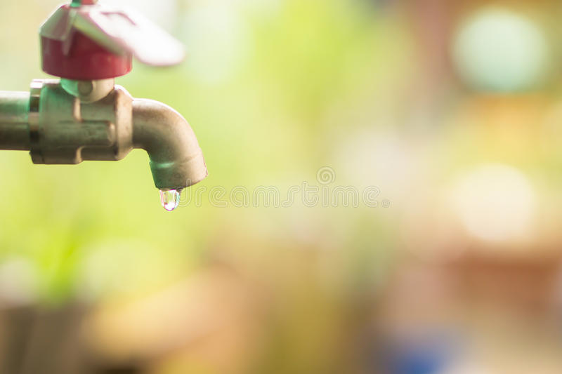 Close up water drop from tab, leaking water, save water and water conservation concept stock photography