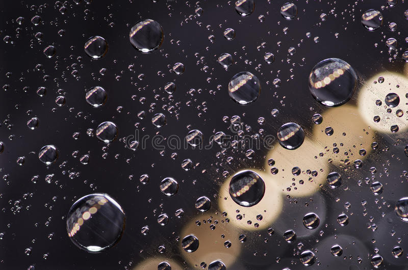 Close-up on water drops background on creamy and black surface. Water droplets with reflections in them stock photos