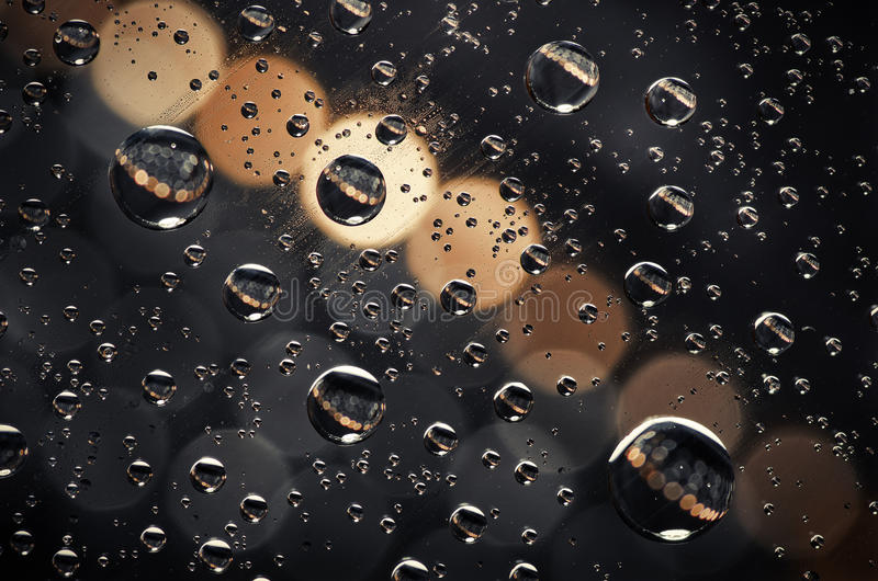 Close-up on water drops background on creamy and black surface. Water droplets with reflections in them royalty free stock photos