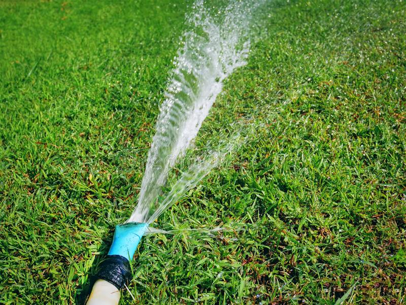 Water Hose Spraying Water on Green Grass Field royalty free stock photography