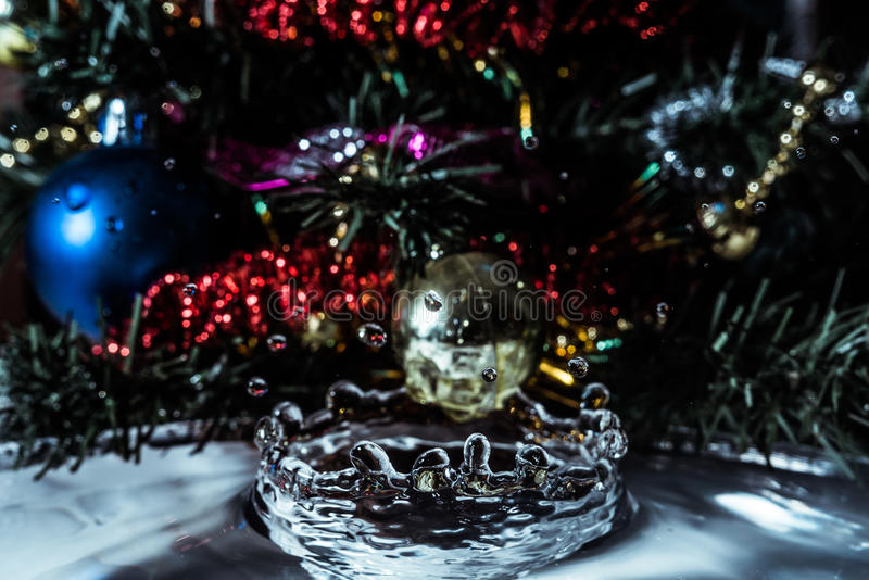 Close-up of water splash crown from tinsel, fir and Christmas toys. Holidays background royalty free stock photo