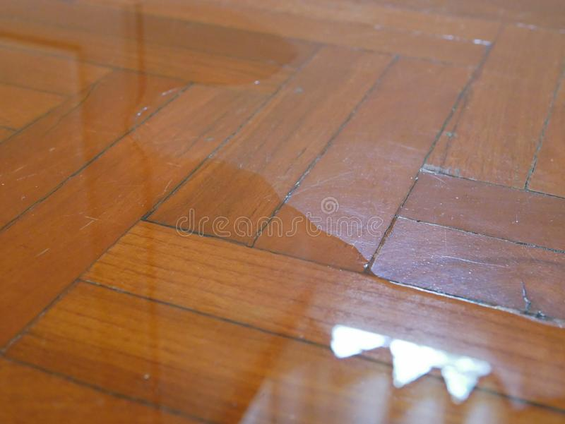 Close up of water spreading / flooding on the parquet floor of a house - damage caused by water leakage royalty free stock photo