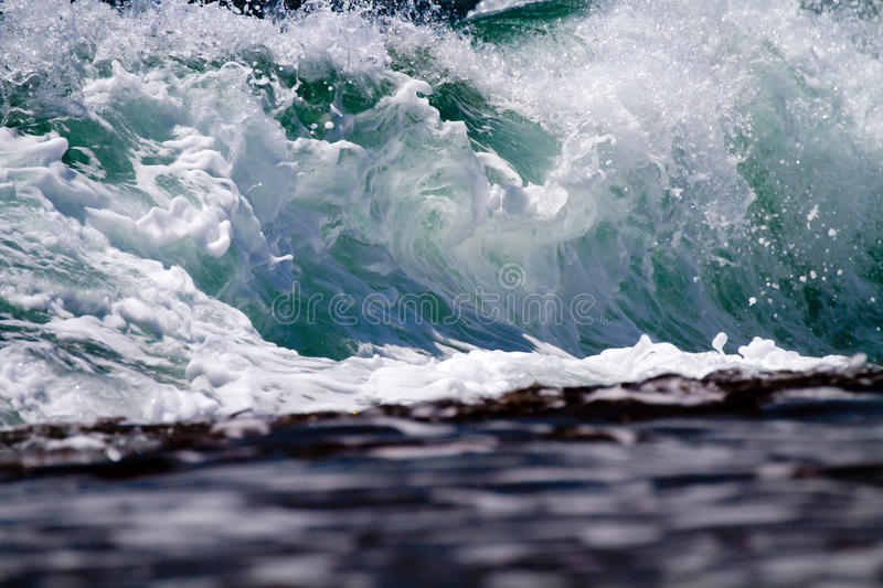 Close Up Wave Breaking On Shore. A close up image of a wave breaking onto a reef in Kauai, Hawaii royalty free stock images